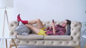 Mulher relaxado que verifica seu telefone celular no sofá filme