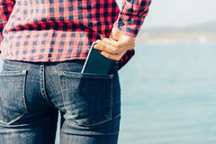 A mulher remove o smartphone de seu bolso traseiro das calças de brim Foto de Stock Royalty Free