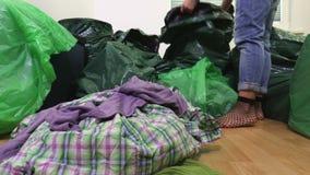 A mulher remove a roupa dos sacos de plástico video estoque