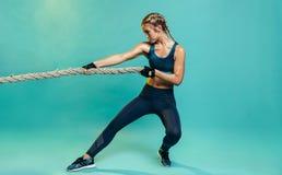 Mulher resistente dos esportes que exercita com corda de luta imagens de stock