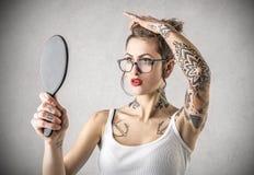 Mulher resistente nova com as tatuagens que guardam um espelho Fotografia de Stock Royalty Free