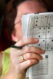 A mulher resolve Sudoku Imagens de Stock Royalty Free