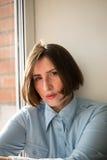Mulher restrita com sinal de intercalação do cabelo curto na camisa azul imagens de stock
