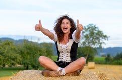 Mulher retirada feliz que senta-se em um pacote de feno Fotos de Stock