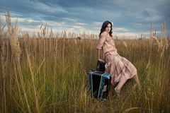 A mulher retro está sentando-se no campo Foto de Stock