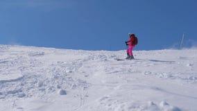 A mulher rola lentamente para baixo o esqui da montanha em uma inclinação íngreme com pedregulhos filme