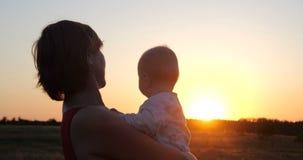 Mulher romântica com uma criança nas mãos que olham o por do sol no arquivada no slo-mo video estoque