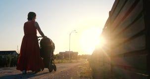 Mulher romântica em um vestido vermelho que monta sua criança em um pram no por do sol imagens de stock royalty free
