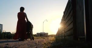 Mulher rom?ntica em um vestido vermelho que monta sua crian?a em um pram no por do sol no slo-mo vídeos de arquivo