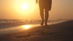 Mulher romântica que anda na costa de mar com os pés descalços no por do sol no movimento lento com efeitos do alargamento da len filme