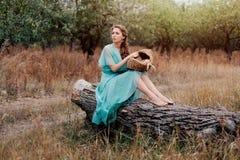 Mulher romântica que veste o vestido elegante longo que senta-se no campo, estação do outono, abrandamento no campo, apreciando a Fotos de Stock Royalty Free