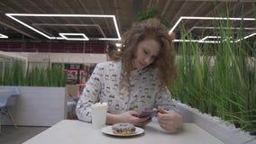 A mulher ruivo bonita nova no estilo ocasional senta-se em um café com café e filhós video estoque