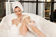 A mulher ruivo bonita nova toma o banho de espuma imagens de stock