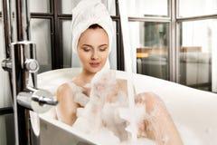 A mulher ruivo bonita nova toma o banho de espuma fotografia de stock royalty free
