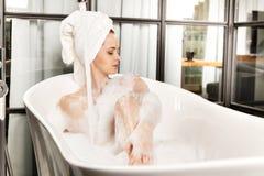 A mulher ruivo bonita nova toma o banho de espuma foto de stock