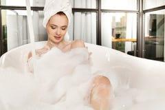 A mulher ruivo bonita nova toma o banho de espuma foto de stock royalty free
