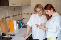 A mulher ruivo ensina a uma m?e idosa como usar um smartphone Mãe e filha adulta vestidas nas blusas brancas fotografia de stock