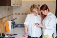 A mulher ruivo ensina a uma m?e idosa como usar um smartphone Mãe e filha adulta vestidas nas blusas brancas imagem de stock