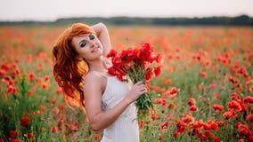 Mulher ruivo nova bonita no campo da papoila que guarda um ramalhete das papoilas Foto de Stock