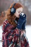Mulher ruivo nova em fones de ouvido e em luvas azuis Fotografia de Stock Royalty Free