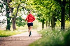 Mulher running, apreciando o dia de verão no parque Foto de Stock