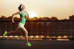 Mulher Running O corredor está movimentando-se no nascer do sol Modo fêmea da aptidão Imagem de Stock Royalty Free