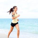 Mulher running que movimenta-se na praia que escuta a música imagens de stock royalty free