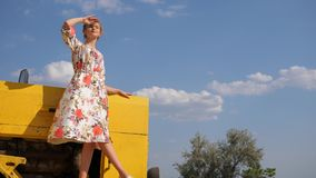A mulher rural nova no vestido olha na distância que está à capota do trator na natureza vídeos de arquivo