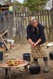Mulher rural superior que prepara a galinha exterior Fotografia de Stock