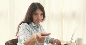 Mulher séria adulta que aponta na câmera filme
