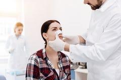 Mulher séria agradável que tem um molho médico em seu nariz fotos de stock royalty free