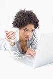 Mulher séria com copo de café usando o portátil na cama Fotografia de Stock