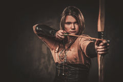 A mulher séria de viquingue com curva e seta em um guerreiro tradicional veste-se, levantando em um fundo escuro fotos de stock royalty free
