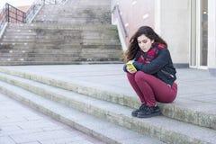 Mulher séria e pensativa que usa o telefone celular, assento de s imagem de stock