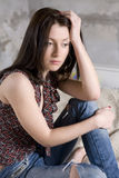 mulher séria nas calças de brim que têm o furo sentar-se em s Foto de Stock