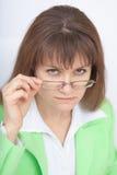 Mulher séria - o professor olha-nos sobre vidros imagem de stock