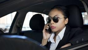 Mulher séria que fala no telefone no carro, detetive privado que espia, agente de polícia imagens de stock royalty free