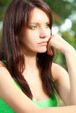 Mulher séria que senta-se sob a face do close up da árvore imagens de stock