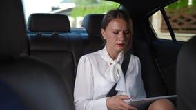 Mulher séria que usa a tabuleta que vai trabalhar pelo táxi video estoque