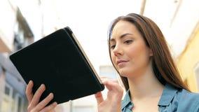 Mulher séria que usa uma posição da tabuleta na rua vídeos de arquivo