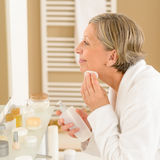 A mulher sênior aplica a loção da limpeza da face Fotos de Stock Royalty Free
