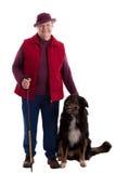 Mulher sênior ativa com vara e cão de passeio fotos de stock royalty free