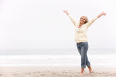 A mulher sênior com braços Outstretched na praia