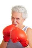 Mulher sênior com luvas de encaixotamento fotografia de stock royalty free