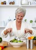 Mulher sênior feliz que cozinha uma salada Foto de Stock Royalty Free