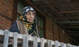 Mulher sênior na casa velha da avó do balcão fotografia de stock royalty free
