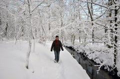 Mulher sênior que anda ao lado de um rio pequeno Fotos de Stock