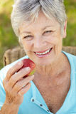 Mulher sênior que come a maçã Fotos de Stock Royalty Free
