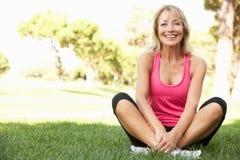 Mulher sênior que descansa após o exercício no parque