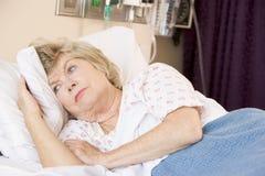 Mulher sênior que encontra-se na cama de hospital Imagens de Stock